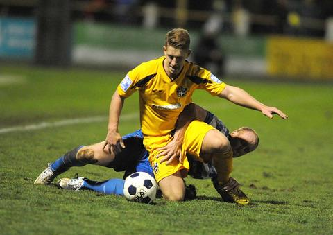 Oxford City's Andy Ballard gets to grips with Sutton United's Sam Rents