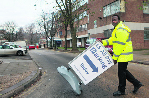 Efosa Nehiweze puts out a sign for the car park at Oxford & Cherwell Valley College's Oxpens campus in Oxford