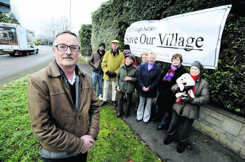 Neil Evans, left, chairman of KBS Village Action, with other locals by the busy mini roundabout at the top of Kingston Bagpuize where they have put up a banner as part of a campaign against the planned number of new homes