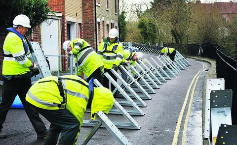 Environment Agency workers build flood barriers in West Street on Osney Island yesterday