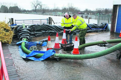 Paul Einon and Andrew Whittington of Oxford City Council check the pump in Bullstake Close, West Oxford