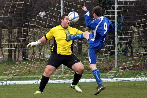 Stonesfield's Pete Searle lobs keeper David Newbold in their 4-2 victory at home to Marston Saints in Division 1