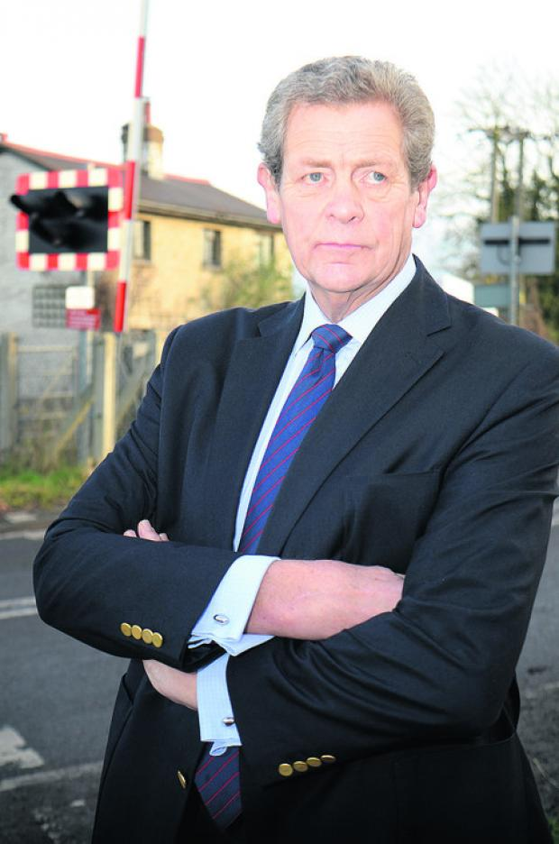 Oxford Mail: Parish council chairman Michael Gibbard at the level crossing in Sandy Lane. Picture: OX56625 Marc West