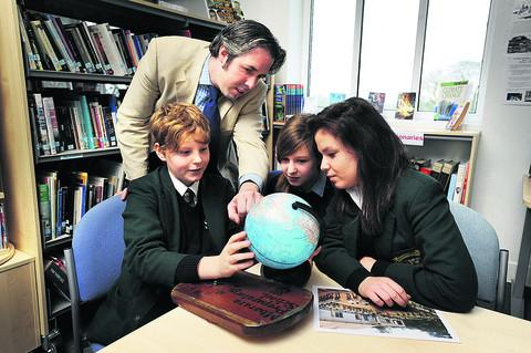 Sibford School teacher Edward Rossiter shows pupils Spencer Farley, 12, Lizzy Hudson, 11, and Jess Edwards, 13, Uganda, where Mbarara Preparatory School is located