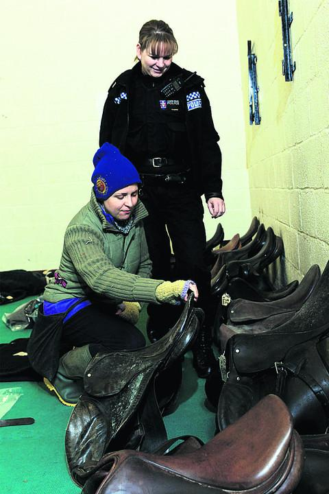 Tack theft victim Issy Whitford looks at some of the recovered items with Pc Sharon Harris
