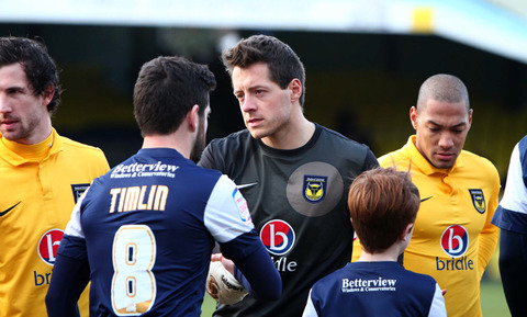 New Oxford United goalkeeper Luke McCormick (centre) shakes hands with Southend United's Michael Timlin before kick-off