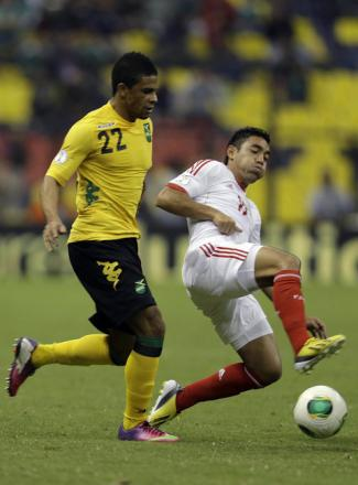 Jamaica's Garath McCleary (left) battles for the ball with Mexico's Severo Meza