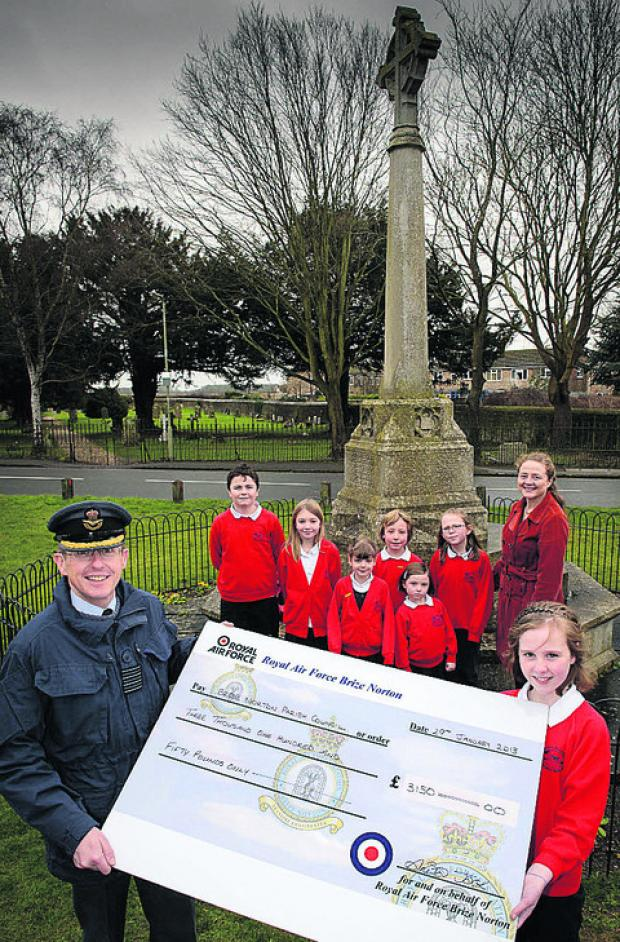 Group Captain Eddie Cole at the memorial with pupils from Brize Norton Primary School and parish clerk Carolyn Peach