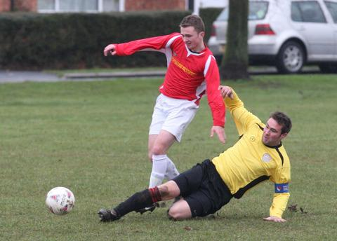 Wootton & Dry Sandford's four-goal hero, Luke Ingram (left) is stopped in his tracks on this occasion by Benson's Will Clements