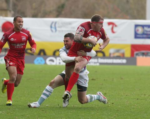London Welsh hooker Neil Briggs looks for support as he is tackled by London Irish fly half Ian Humphreys