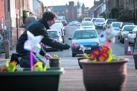 Phil Gauron installs planters at the chicane in Lime Walk, Headington, as part of a neighbourhood campaign to get drivers to heed the 20mph limit. Picture: OX57451 Andrew Walmsley