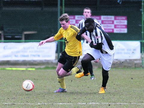 North Leigh goalscorer, Declan Shepperd (right), battles for the ball with a Wimborne opponent