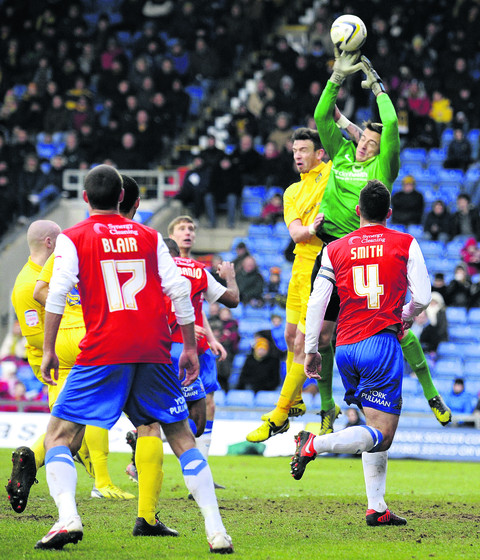 Michael Raynes challenges keeper Michael Ingham for a high ball