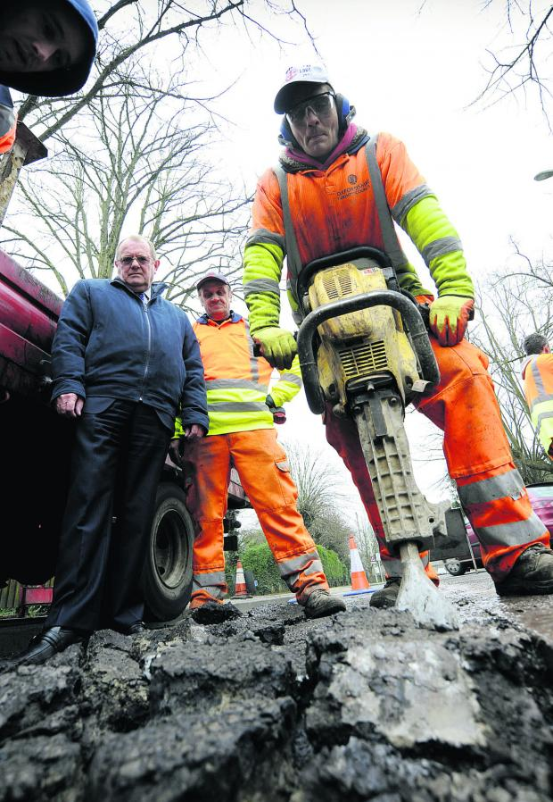 Stuart Lucas operates a jackhammer as county transport cabinet member Rodney Rose, left, looks on with Gary Maddison