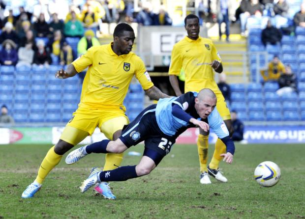 United striker Jon-Paul Pittman sends Wycombe's Michael Harriman crashing to the ground