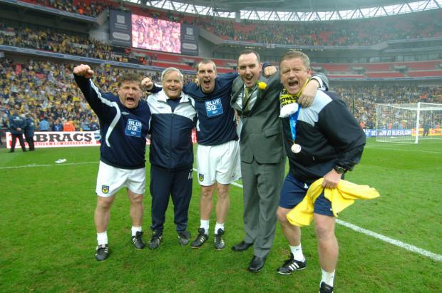 Oxford Mail: Chris Wilder celebrates winning promotion at Wembley with his backroom team and chairman Kelvin Thomas