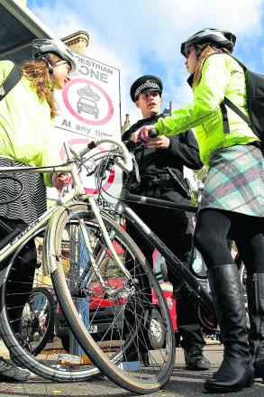 Sgt Matt Sulley discusses bicycle safety with students Helen Please, 24, left, and Julia Graham, 25. Picture: OX62637 Ric Mellis