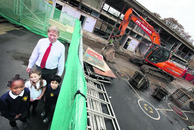 Headteacher Keith Ponsford and pupils, from left, Miriam Atolabi, six, Sophie Lygo Wilks, five, and Theo Magallano, five, watch as work starts on the school revamp