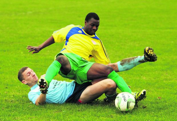 Garsington's Ash Burristo (in yellow) is slide tackled by Rick Armstong of Chalgrove in their Premier Division clash   Pictures: Damian Halliwell Order no: OX62978