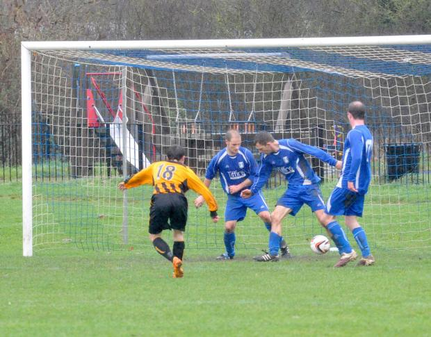 Drayton's Ashley Seamark slips the ball into the net, despite the desperate attempts of three Sutton Courtenay defenders to prevent it from going in