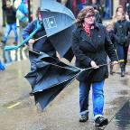Oxford Mail: Shoppers struggle with their brollies at Carfax as high winds and heavy rain swept the county yesterday