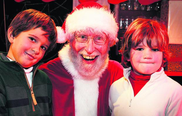 Richard Evans, who played Santa, meets Jack Lund, six, left, and his brother Oliver, four