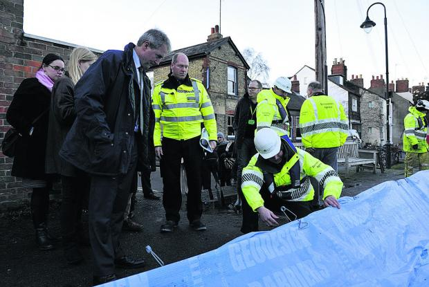 Oxford Mail: Environment Secretary Owen Paterson is shown the flood defences at Oxford's Osney Island by Al Wells of the Environment Agency