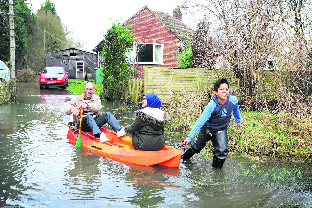 Fokhrul Dewan and his children, Tasnin, 17, and Riyadh, 10, leave their Fox Crescent home in a canoe. Picture: OX64593 Jon Lewis