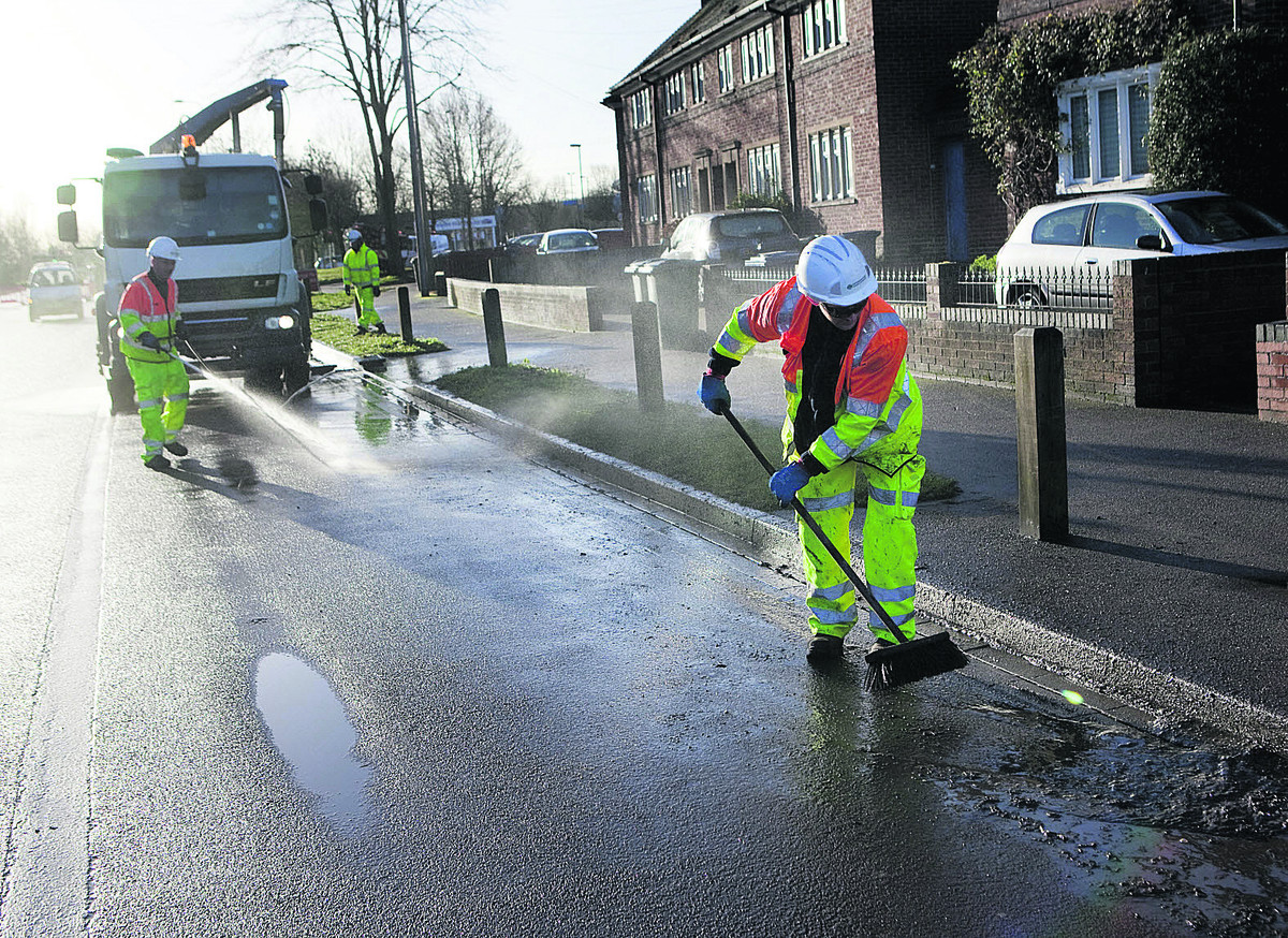 Oxfordshire County Council staff John Sellar, left, and Rob Pardy clean away debris from Abingdon Road ahead of its reopening to traffic yesterday
