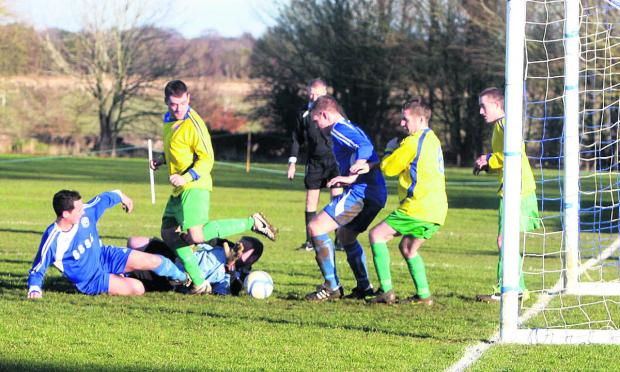 Garsington goalkeeper Steven Simmons scambles for the ball as Stonesfield pile on the pressure