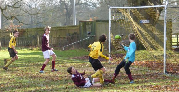 Oxford Mail: Ryan Holmes (15) scores one of North Leigh's goals in their 11-1 home win against Bourton Rovers Youth in the Under 14 A League encounter, despite a strong challenge from a visiting defender