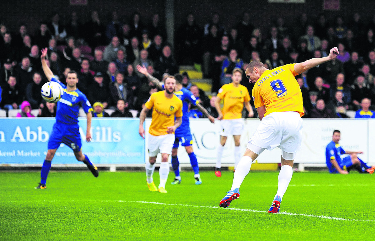 James Constable heads in the opening goal of October's meeting with AFC Wimbledon, while the home defenders appeal in vai