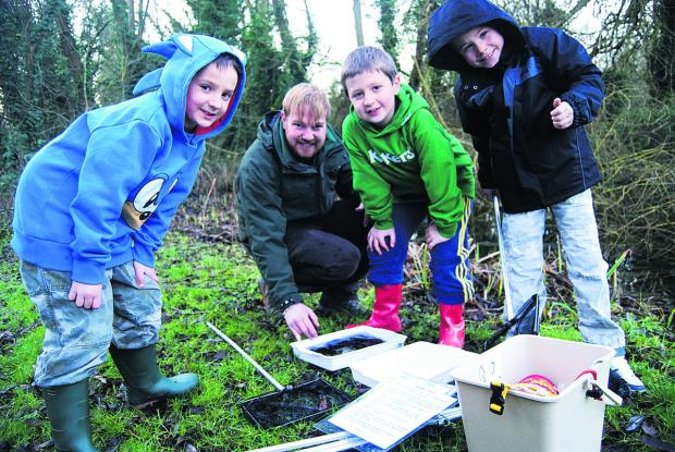 From left, Josh Ballard, six, Max Ballard, eight, and Arun Baggett, eight, try pond dipping with project manager Andy Gunn