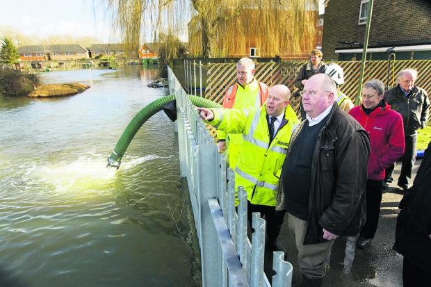 Eric Pickles, right, surveys the floods behind Bullstake Close, off Botley Road, with Oxfordshire County Council chairman Ian Hudspeth