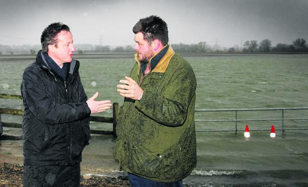 Oxford Mail: David Cameron visits farmer Tim Hook at his flooded fields near Bampton