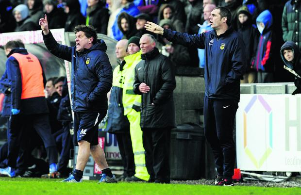 Oxford United's caretaker manager, Mickey Lewis (left), and first-team coach Andy Melville on the touchline urging their side to make the most of their remaining games
