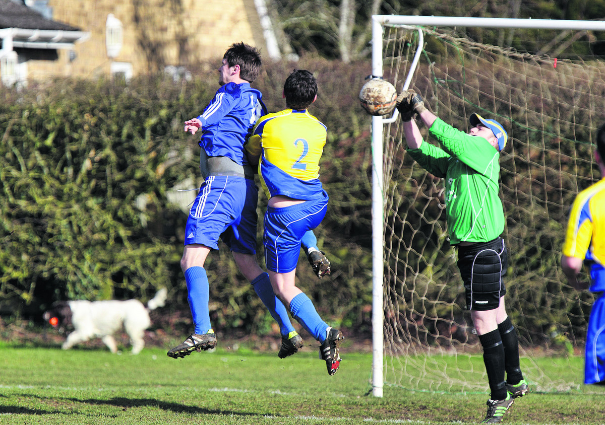Ducklington goalkeeper Ashley Edwards saves a header from Witney Royals' Chris Catchpole (left) following a corner kick, despite the challenge of Dan Malony
