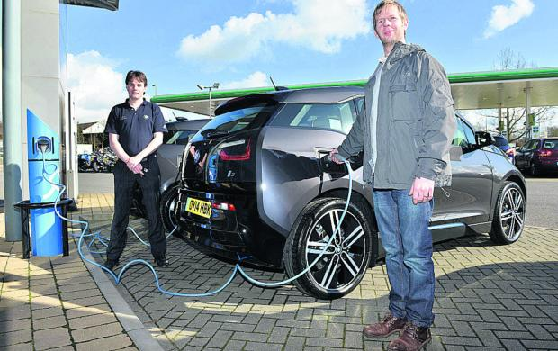 Oxford Mail: John Ganderton, right, with his new BMW electric car with John Gibbons of BMW North Oxford Garage   Picture OX65436 Simon Williams