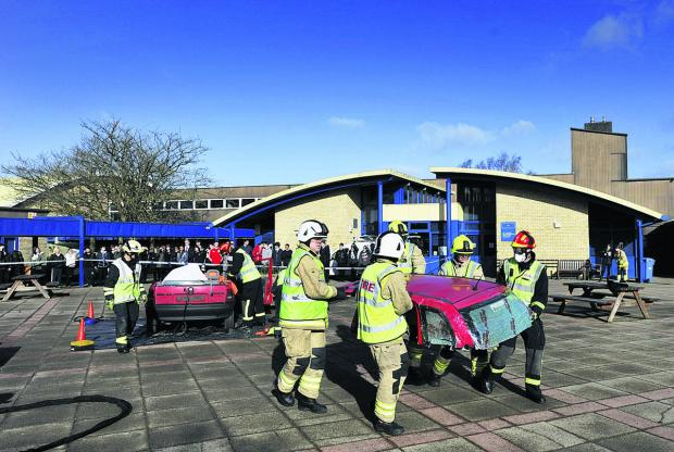Oxford Mail: Firefighters move the roof out of the way after cutting it from the wrecked car to free the trapped 'casualty'