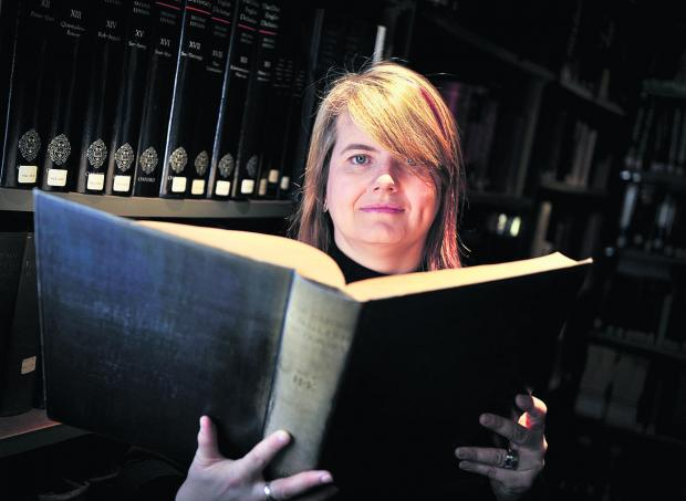 Fiona McPherson with a 1928 edition of the Oxford English Dictionary