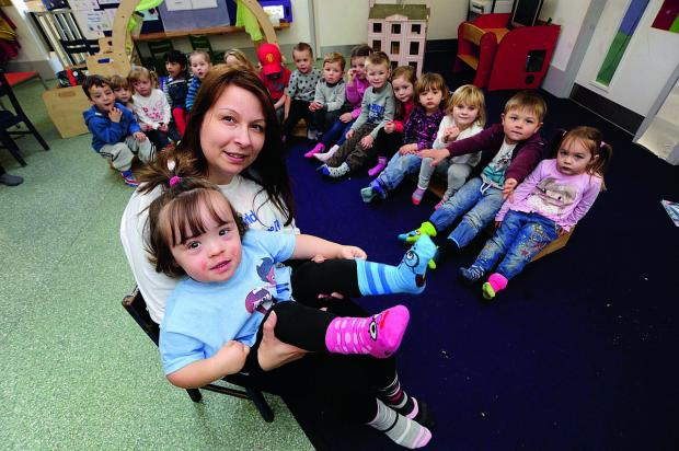 World Down's Syndrome Day is marked at Berinsfield Pre-School with all the children wearing odd socks. Front, Jo Crawford with her daughter Evie-Mae, two, wearing her odd socks, with her friends offering their efforts