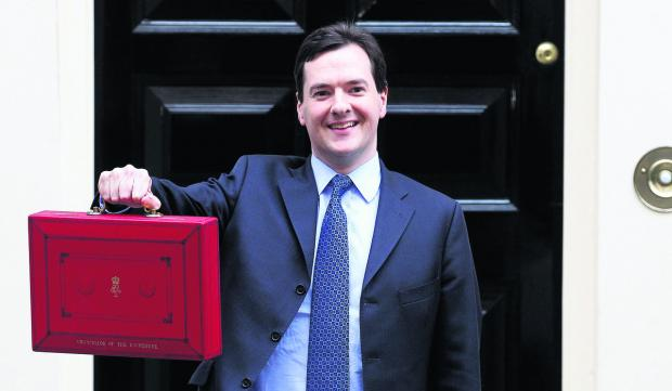 CHANGES: Chancellor George Osborne holds up his red Ministerial Box outside 11 Downing Street before heading to the House of Commons to deliver his annual Budget statement