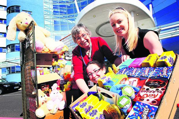 Oxford Mail: Penny Hambridge, left, of Oxford Children's Hospital, receives the Easter eggs from Alicia Medlicott and Alice Clarke, of recruitment firm Reed. Picture: OX66337 Ed Nix
