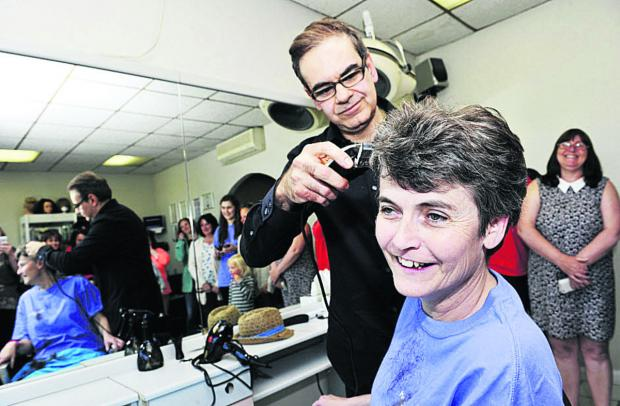 Ellie Thompson is supported by colleagues as her head is shaved by Charles Tracoshas, of Gemini Hair, in Bicester. Pictures: OX66578 Mark Hemsworth