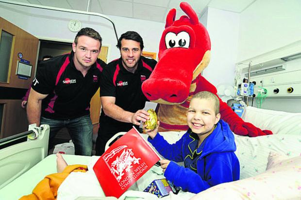 London Welsh players James Tideswell, left, and Nathan Vella join Dewi the Dragon to present Josiah Andrews, 13, with an Easter egg. Picture: OX66640 David Fleming
