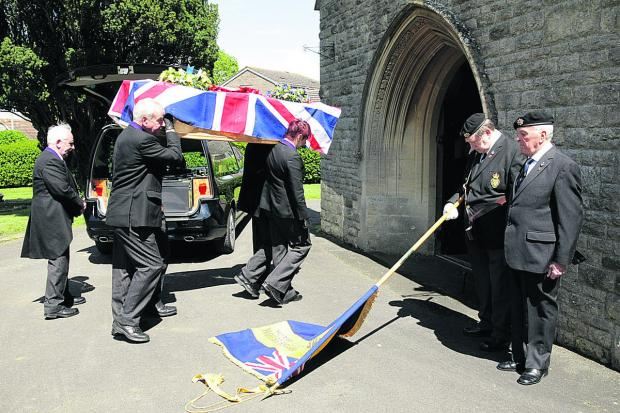 The coffin of D-Day veteran and lifelong Oxford United fan, George Bateman is carried into the chapel at Headington Cemetery, Oxford