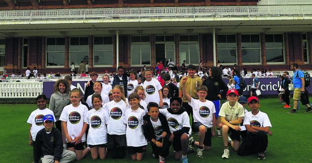 The lucky pupils from St Mary and St John Primary School pose for a picture in front of the pavilion at Lord's