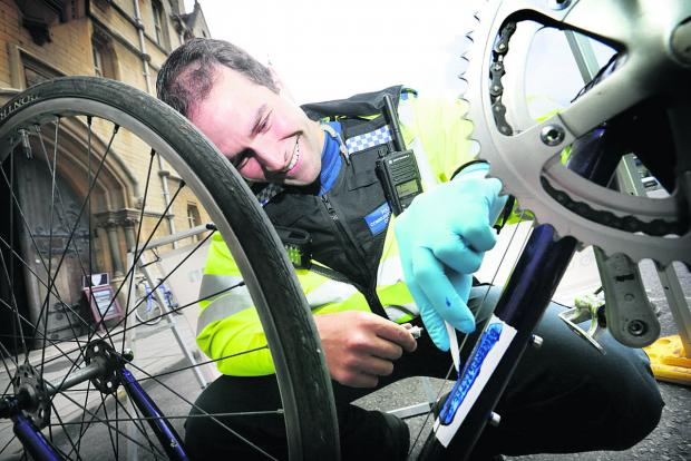 PCSO Matt Autery security-marks a bike in Broad Street. Picture: OX67364 Damian Halliwell