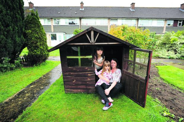 Angharad Holloway with daughters Eleanor, seven, and Anwen, three, in the Wendy house which needs planning permission