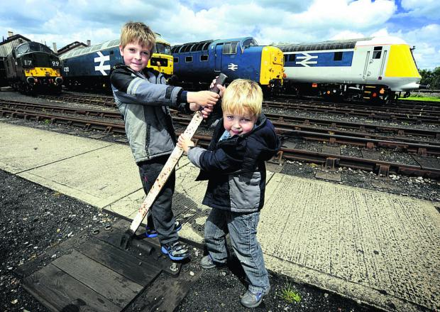 Oxford Mail: Joshua Hogg, eight, and his four-year-old brother Nathan with a line-up of locomotives at Didcot Railway Centre's Diesel Gala on Saturday	       Picture: OX67427 David Fleming